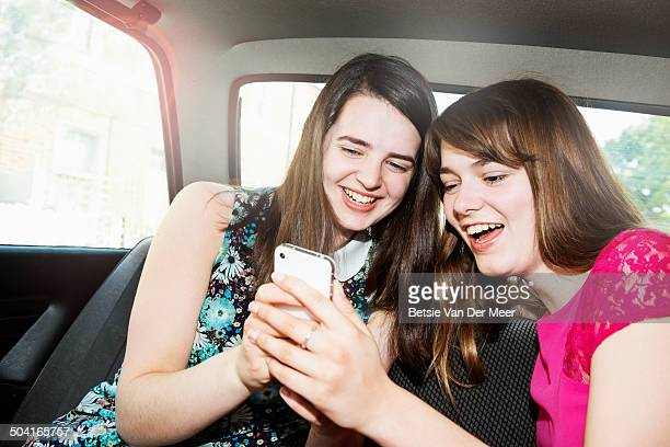 girls looking at mobile phone in car.