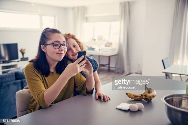 Girls looking for a banana cake recipe on mobile phone.