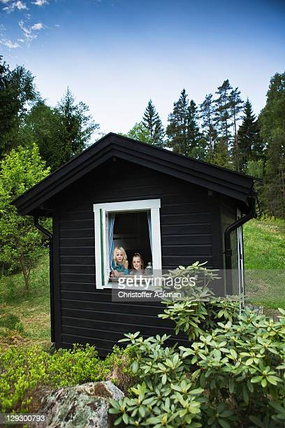 Girls looking out window of shack