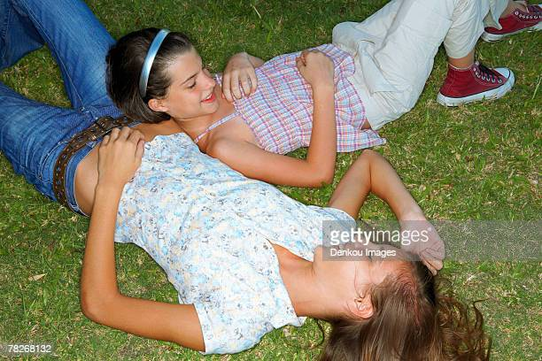 girls lying down in the garden. - down blouse stock pictures, royalty-free photos & images