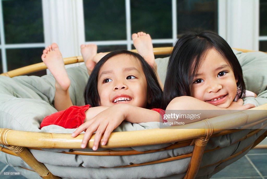 Girls Lying In Papasan Chair : Stock Photo