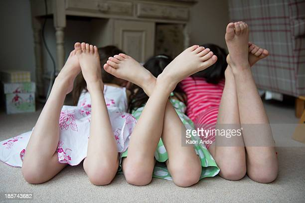 girls lying on floor together with feet up - barefoot feet up lying down girl stock photos and pictures