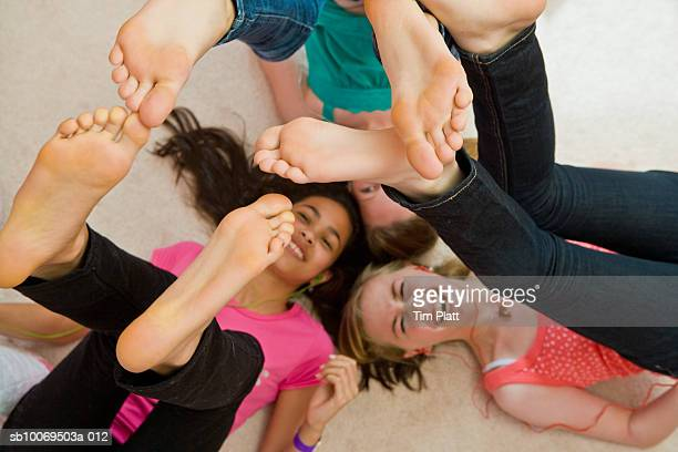 Girls (12-13) lying on floor with feet in air