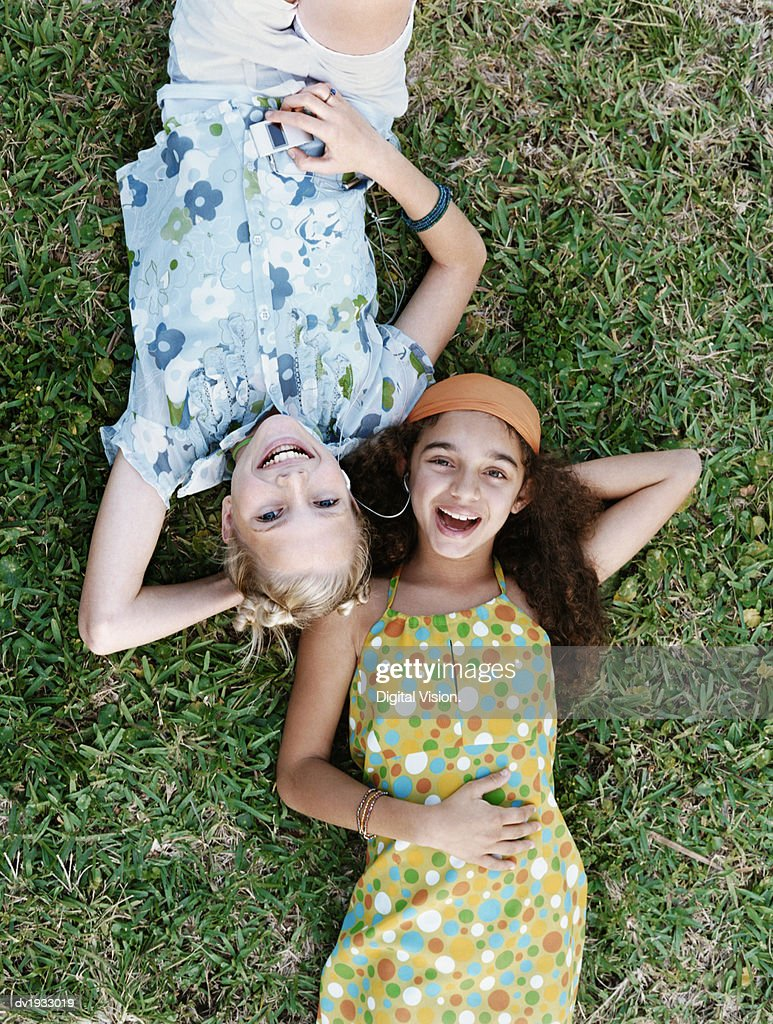 Girls Lying on Grass With Their Hands Behind Their Heads : Stock Photo