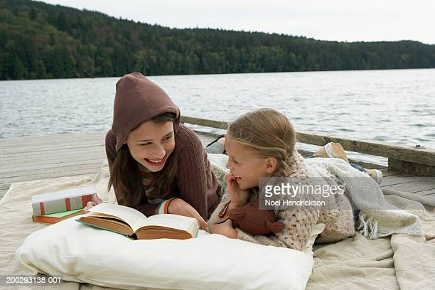 girls (6-13 years) lying on rug on jetty beside lake, reading book and laughing - 14 15 years stock pictures, royalty-free photos & images