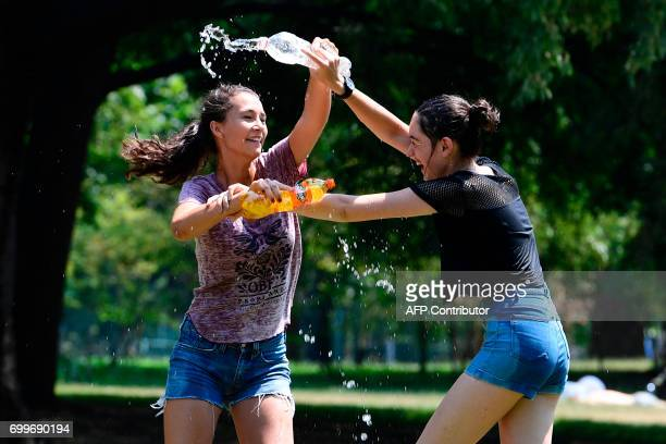 Girls make a water battle with plastic bottles on June 22, 2017 in a garden of Milan on a hot summer-day. In Italy, forecasters say the current...