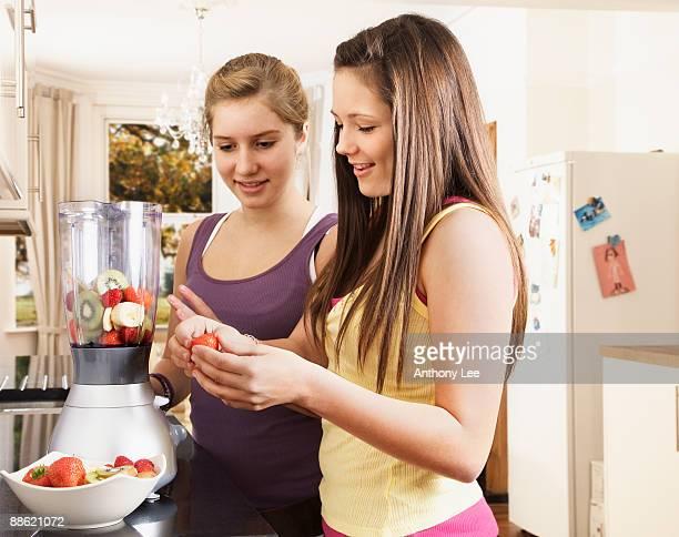 girls making fruit smoothie in kitchen - rijp voedselbereiding stockfoto's en -beelden