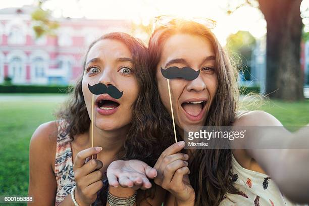 Girls making selfie with stache-on-a-stick