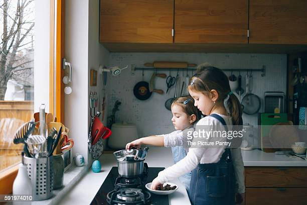 Girls melting chocolate in a kitchen