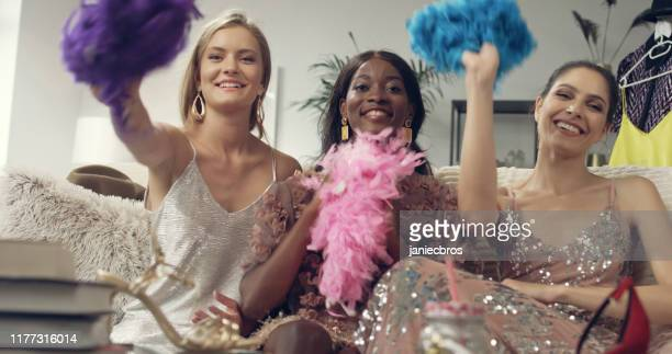 girls night fun. multi ethnic friends throwing boas - boa stock pictures, royalty-free photos & images