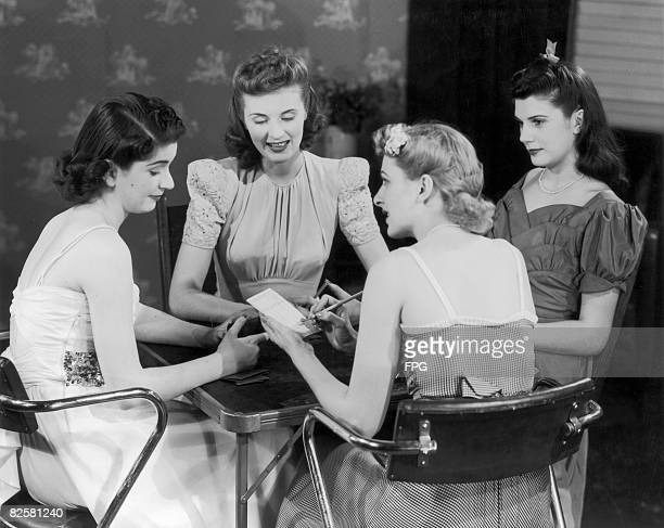 Circa 1950, Four young ladies gather round a card table for an evening of fun.