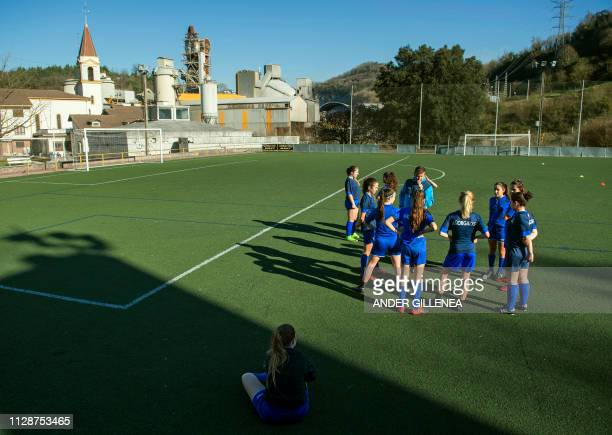 Girls of Anorga KKE football school listen to a coach during a training session in the Spanish Basque city of San Sebastian on February 27 2019