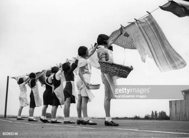 Girls of the domestic school in Ongar, Essex hanging up the laundry, Photograph, Oct, 9th 1937 [M?dchen beim Aufh?ngen von W?sche in der...