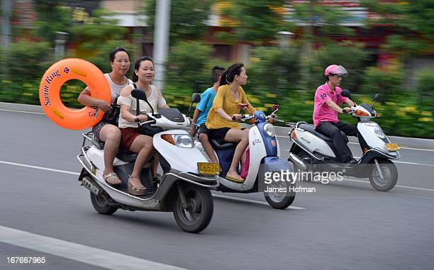 CONTENT] Girls on speeding motor scooters carrying a large swim ring in Yanjiang China