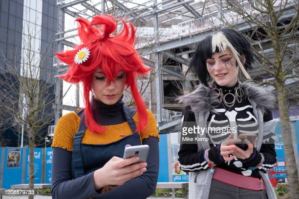 Girls on their smartphones dressed up for a day out in their Cosplay guises Nao Egokoro with red hair and Reko Yabusame, from the video game 'Your...