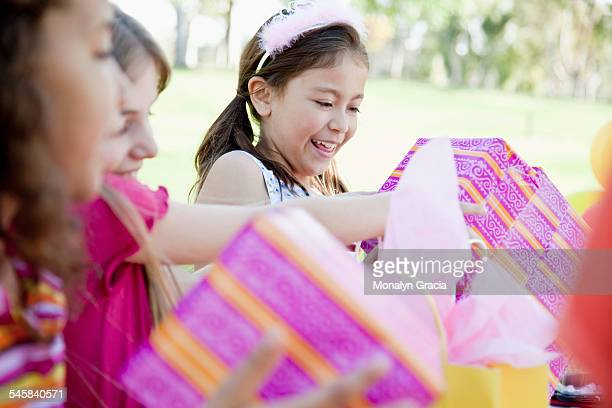Girls (7-9) opening birthday presents in park