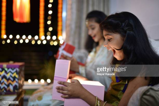 girls opening gift boxes received on the occasion of diwali - gifts stock pictures, royalty-free photos & images