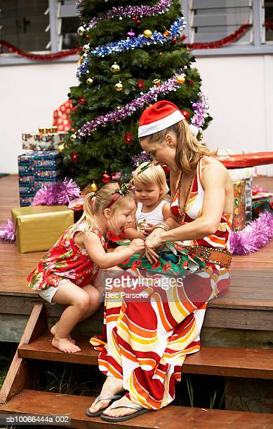 Girls (1-3) opening presents with mother by Christmas tree on porch