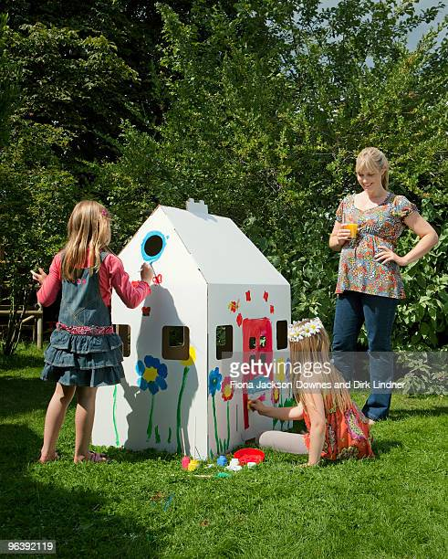 Girls painting a cardboard wendy house