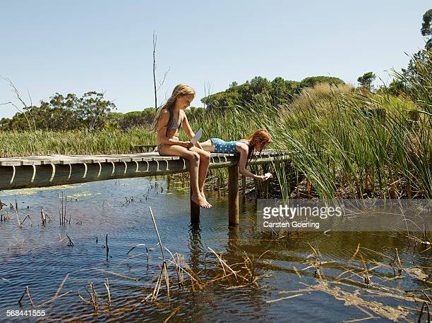 2 girls palying on a jetty