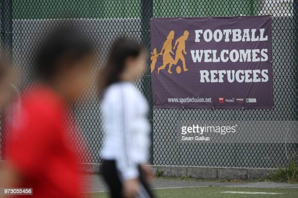 Girls participate in a training day in a program to encourage integration of children with foreign roots through football near a sign that reads...