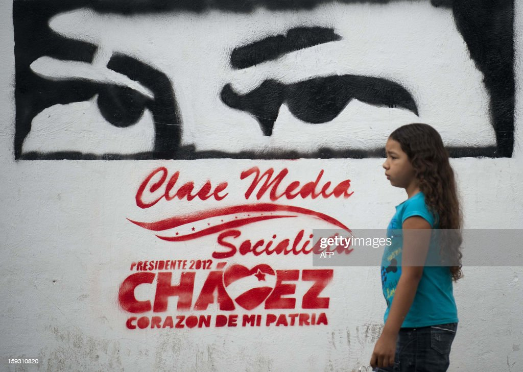 A girls passes by a stencil mural about Venezuelan President Hugo Chavez in Caracas, on January 11, 2013. With Chavez ailing and absent, Venezuela's leftist government launches a new presidential term with a display of popular support on the day he was to be inaugurated. The Supreme Court cleared the cancer-stricken president, who is recovering from a fourth round of cancer surgery in Havana, to indefinitely postpone his re-inauguration and said his existing administration could remain in office until he is well enough to take the oath. AFP PHOTO/Raul ARBOLEDA