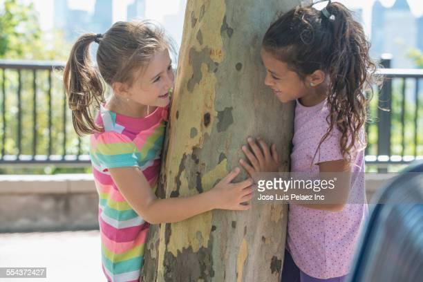 girls peeking around tree in park - 6 7 anni foto e immagini stock