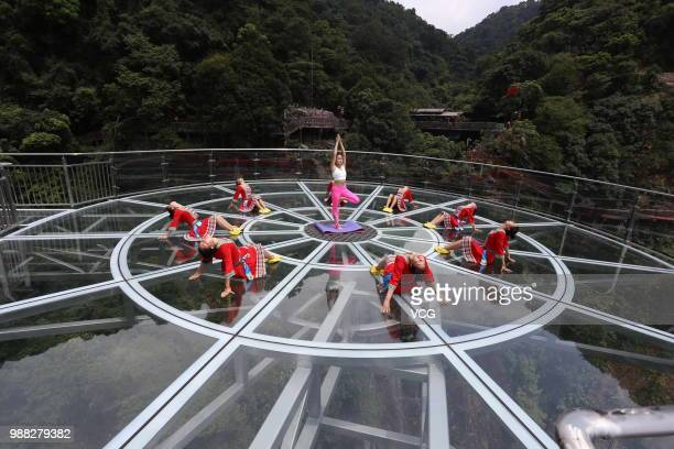 Girls perform yoga on a glass bridge featuring a circular observation deck along a cliff at the Gulongxia scenic spot on June 27 2018 in Qingyuan...
