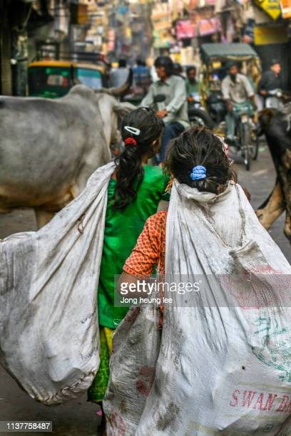 Girls picking up recyclables on the streets of India.
