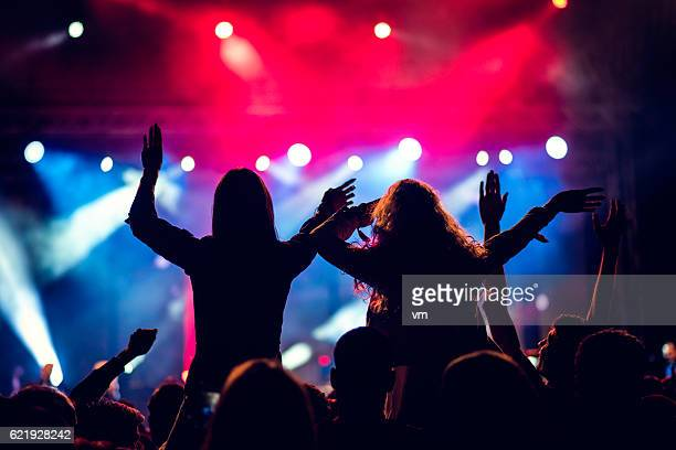 Girls piggyback riding at a concert