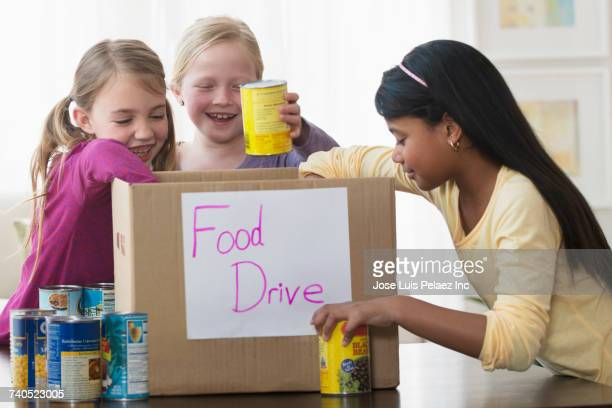 girls placing cans of food in donation box - food drive stock pictures, royalty-free photos & images