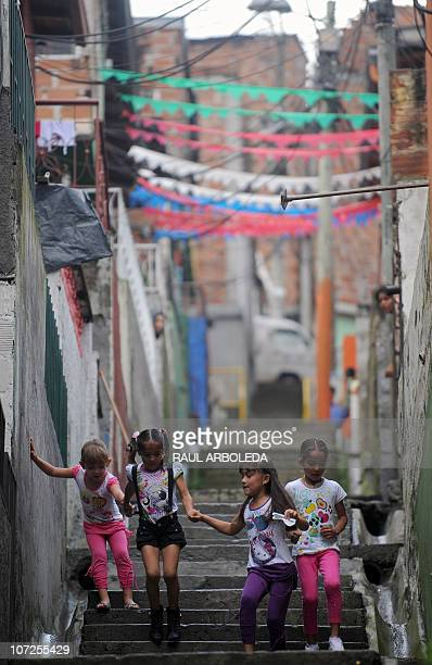 Girls play in the stairs of Pablo Escobar neighborhood on December 1 2010 in Medellin Antioquia department Colombia on the anniversary of the birth...