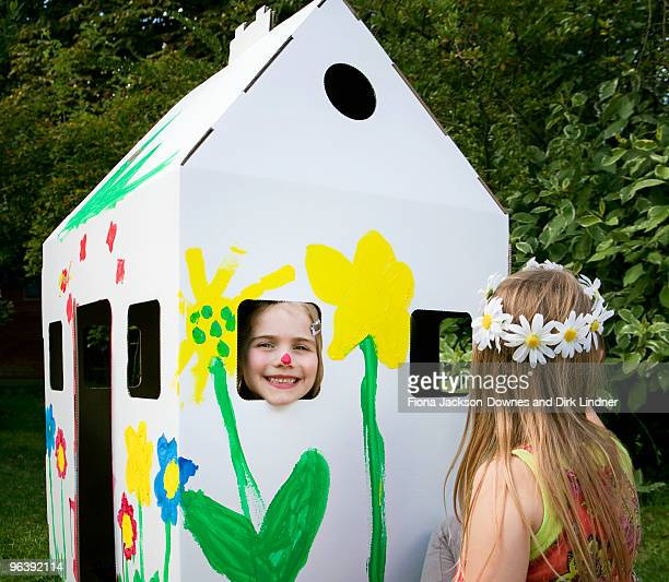 Girls play with a cardboard wendy house