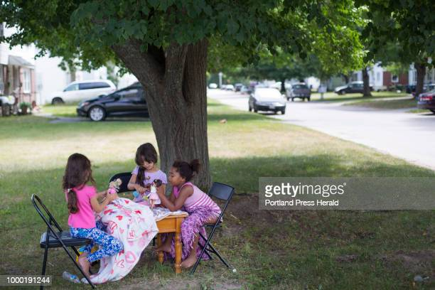 Girls play with dolls at a table set up in a yard at Sagamore Village in Portland near the proposed site of a new homeless service center