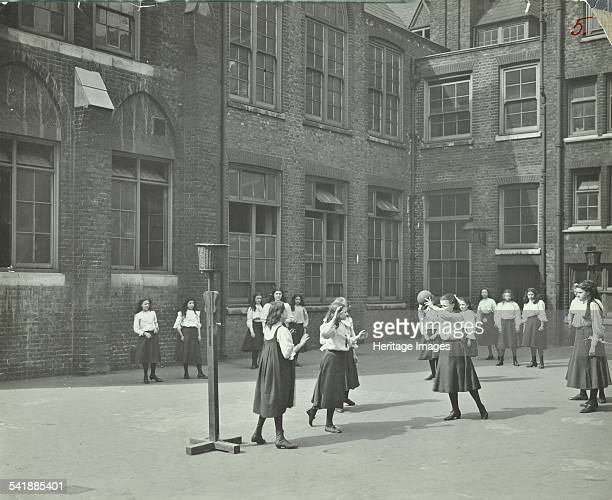 Girls playing basketball in the playground, William Street Girls School, London, 1908. The girl with the ball is poised ready to shoot a goal....