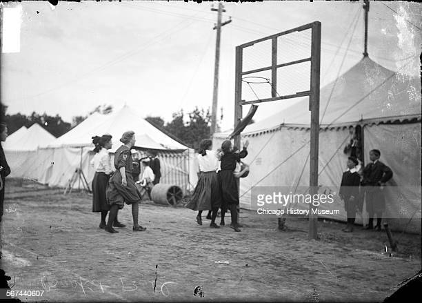 Girls playing basketball on a grass court surrounded by light colored tents, Chicago, Illinois, 1905. A group of boys is standing near the basket,...
