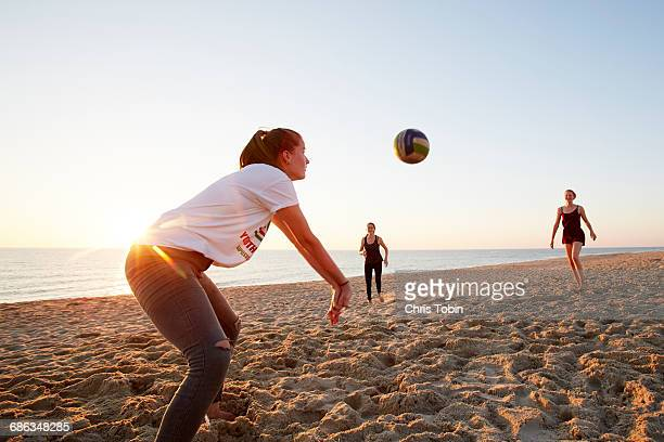 girls playing beach volleyball - beachvolleybal stockfoto's en -beelden
