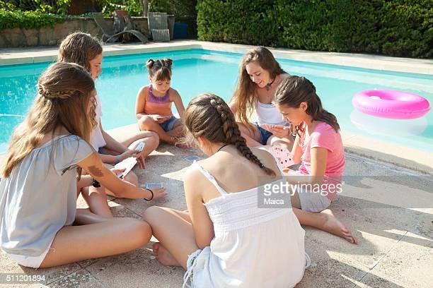 Mädchen Spielkarten im Sommer mit einem Schwimmbad