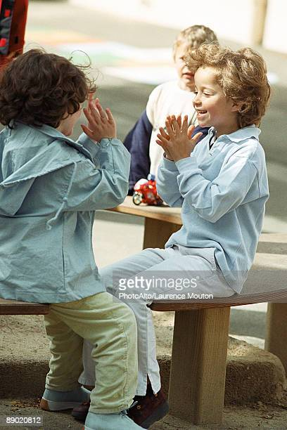 Girls playing clapping game on bench