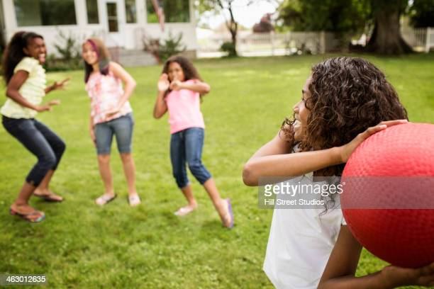 Girls playing dodgeball in backyard