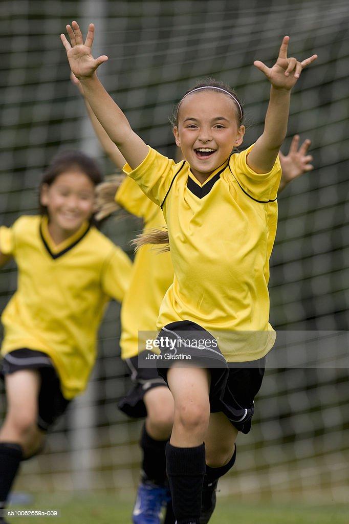 Girls (8-13) playing football, laughing : Stock Photo