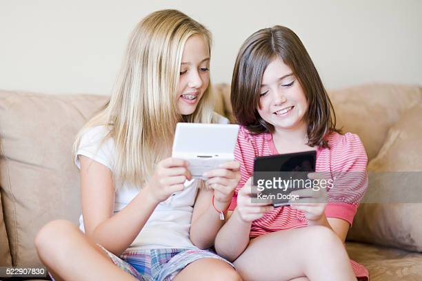 girls playing handheld video games - handheld video game stock pictures, royalty-free photos & images