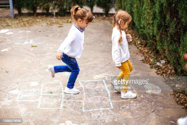 girls playing hopscotch - hopscotch stock pictures, royalty-free photos & images