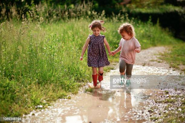 girls playing in mud - playing stock pictures, royalty-free photos & images