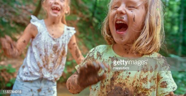 girls playing in mud - wet t shirt girls stock photos and pictures