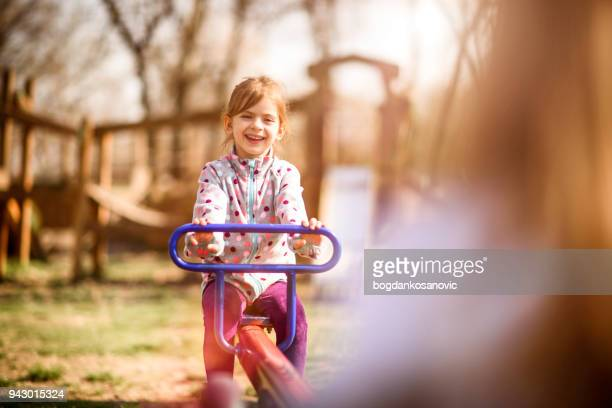 girls playing in the park - seesaw stock photos and pictures