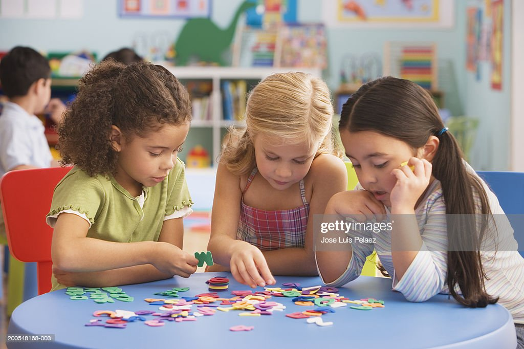 Girls (4-7) playing jigsaw puzzle in classroom : Stock Photo