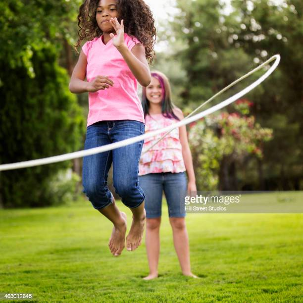 Girls playing jump rope in backyard