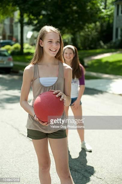 girls playing kickball in a suburban neighborhood - kickball stock photos and pictures