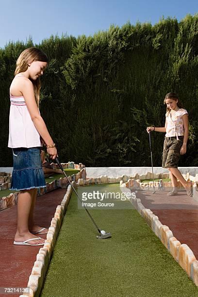 Girls playing miniature golf